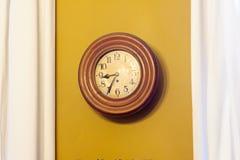 Ockerhaltige Uhr gegen Wand Lizenzfreies Stockfoto