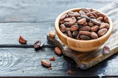 Сocoa beans in wooden bowl closeup. Bowl with organic cacao beans on wooden table, selective focus Stock Photos