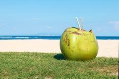 Сoconut with straws on the beach Stock Photo