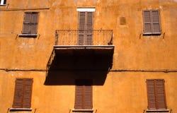 Ocre-Fassade mit Balkon und Schatten Stockbild