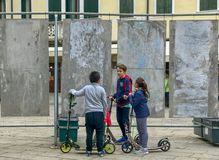 Children on scooters confer on a Venice, Italy, plaza. Oct 2017: Children with push scooters chat on a plaza in Venice, Italy royalty free stock images