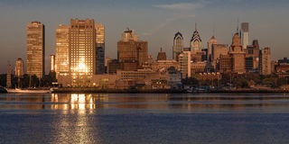 OCT 15, 2016, Philadelphia, PA skyscrappers and skyline at sunrise reflect golden light in Delaware River, as seen from Camden, NJ Royalty Free Stock Photo
