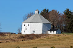 Octagon barn and milk house. An old octagon barn and milk house on a sunny day Royalty Free Stock Photography