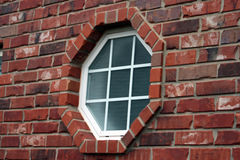 Octagonal Window in Brick. Red brick exterior facade with octagonal shaped window inset.  Window panes are highlighted with white Royalty Free Stock Images