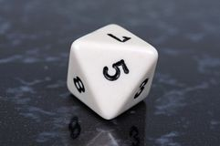 Octahedron shaped dice. White eight sided octahedron shaped dice with black numbers against a dark background Stock Photo