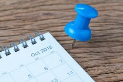 October 2018 calendar appointment, deadline, holiday or date planning concept, big blue pushpin or thumbtack pin on wooden table stock photography