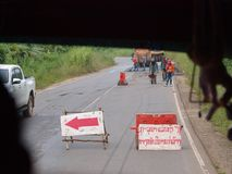 Civil worker repair defect road surface in LAOS. October 15,2017 civil worker repair defect road surface with street signs plates and LAOS alphabets means ` Royalty Free Stock Photos