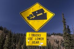 Yellow sign warns truck drivers to slow down on steep mountain r. OCTOBER 2017, Colorado - Yellow sign warns truck drivers to slow down on steep mountain road Royalty Free Stock Photos