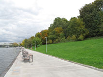 October in the Moscow park. Red, green, yellow trees, benches, road and grey river royalty free stock images