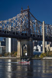 OCTOBER 24, 2016 - NEW YORK - Queens bridge to Roosevelt Island in morning light on East River shows Red Boat Stock Image
