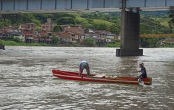 Men in canoes passing the river Antioquia stock image