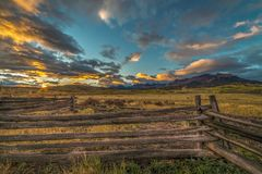 OCTOBER 3, 2018, RIDGWAY COLORADO USA - Sunrise on worm western fence in front of San Juan Mountains in Old West of Southwest stock photo