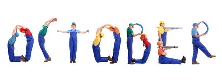 October staff. Group of young people wearing different color uniforms and hard hats forming October word - isolated on white background - calendar concept royalty free stock photos