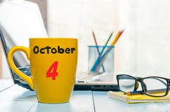 October 4th. Day 4 of month, calendar on yellow cup with yea or coffee, student workplace background. Autumn time stock images