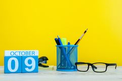 October 9th. Day 9 of month, wooden color calendar on teacher or student table, yellow background . Autumn time. Empty Stock Photos