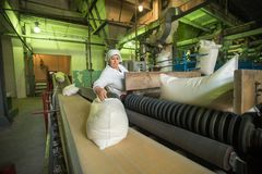 14 october 2014.Ukraine.Kyiv. The woman of average years in a white dressing gown works on a conveyor at factory of times of the stock photos