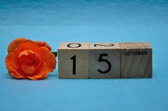 15 October on wooden blocks with an orange rose. On a blue background stock images
