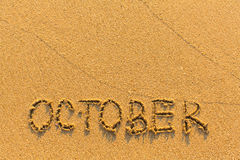 October - word inscription on the gold sand  beach. Royalty Free Stock Image