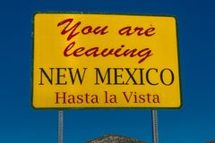 You are leaving New Mexico, Hasta La Vista. OCTOBER 8, 2017 - Yellow state signs says: You are leaving New Mexico, Hasta La Vista Stock Photography