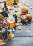 Octoberfest啤酒和快餐在黑暗被烧焦的木背景设置了 图库摄影
