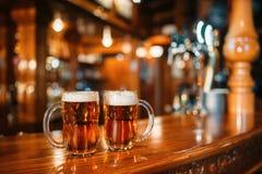 2 кружки пива на деревянном счетчике бара, никто стоковые изображения rf