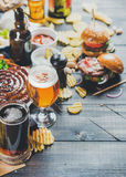 Octoberfest beer and snacks set on dark scorched wooden background. Beer and snack set. Oktoberfest food frame concept. Variety of beers, grilled sausages Stock Photography