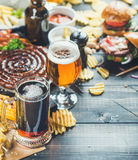 Octoberfest beer and snacks set on dark scorched wooden background. Beer and snack set. Oktoberfest food frame concept. Variety of beers, grilled sausages Royalty Free Stock Image