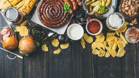 Octoberfest beer and snacks variety on dark scorched wooden background Stock Photo