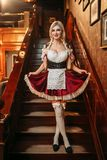 Octoberfest waitress in traditional style dress. On the stairway in vintage pub. Sexy barmaid with attractive shapes in bavarian costume, retro bar royalty free stock photography