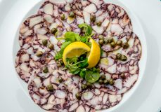 Free OCTOPUS CARPACCIO. Seafood Raw Octopus Slices With Olive Oil, Lemon And Capers On White Plate. Top View. Gray Stone Stock Photo - 127859210