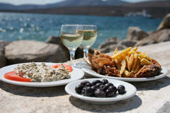 Octopus, chips, olives by the sea Stock Photography
