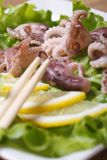 Octopus with lemon wedges and chopsticks macro on a white plate Royalty Free Stock Image
