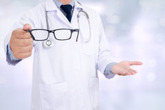 Oculist giving a pair of glasses during a visit, doctor Stock Images