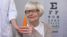 Oculist proposing carrot to smiling elderly lady, natural vitamins for sight. Stock footage stock video