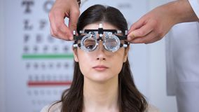 Oculist putting optical trial frame on girl sight correction diopter measurement. Stock footage stock footage