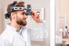Oculista con el dispositivo binocular Imagenes de archivo