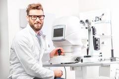 Oculista con el dispositivo oftalmológico Imagenes de archivo