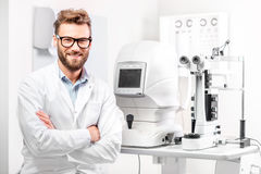 Oculista con el dispositivo oftalmológico Imágenes de archivo libres de regalías