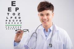 Oculista de sexo masculino asiático que hace una prueba de la vista con la carta de ojo foto de archivo libre de regalías