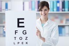 Oculista profesional que lleva a cabo una carta de ojo Imágenes de archivo libres de regalías