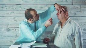 Oculista que comprueba ojos de un paciente masculino mayor 4k almacen de video
