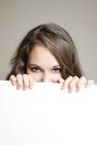 Ocultación adolescente triguena hermosa detrás de muestra. Fotos de archivo