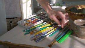 A ocupação do artista, as mãos fêmeas do pintor escolhe a escova perto da paleta das pinturas para tirar no close up do estúdio d filme