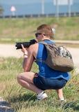 Ocupación del hombre joven con la cámara de SLR Fotografía de archivo libre de regalías