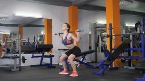 Ocupación deportiva hermosa joven de la muchacha con una barra en un gimnasio del deporte metrajes