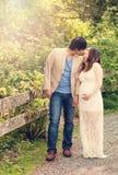 Oczekiwać mamy i tata dzieli romantycznego moment podczas gdy chodzący wewnątrz Zdjęcia Stock