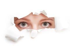 Oczy kobiety zerkanie przez dziury drzejącej w białego papieru plakacie zdjęcie stock