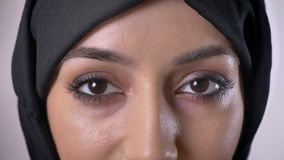 Oczy młoda poważna muzułmańska dziewczyna w hijab oglądają przy kamerą, mruganie, popielaty tło zdjęcie wideo