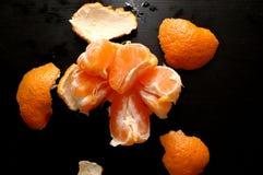 Oczyszczony tangerine na czarnym tle Pożytecznie cytrus obrazy stock