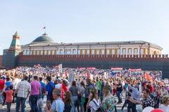 Odödlig regementeprocession i Victory Day - tusentals folk som marscherar längs den röda fyrkanten med flaggor och stående i comm Arkivbild